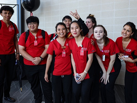 A group of nursing students wearing red and black uniforms