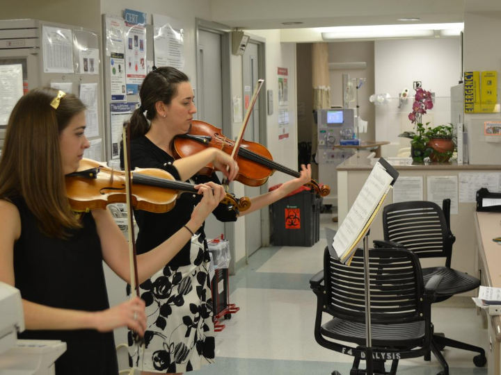 Two women playing violin in the hospital
