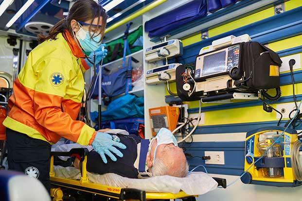 A paramedic attends to an elderly man.