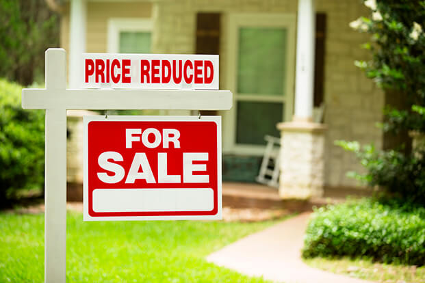 A red For Sale sign placed in front of a house.