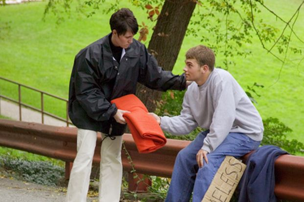 A social worker gives a blanket to a homeless teen.