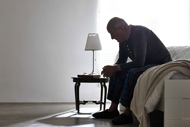 A senior man sits alone on th edge of his bed.