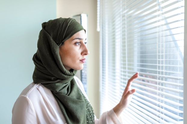 Modern and Young Muslim Woman is Thoughtfully Standing Near the Window in the Domestic Room.                                  Arabian Ethnicity woman is covered with a Traditional Scarf and Looking Through the Window Glass.