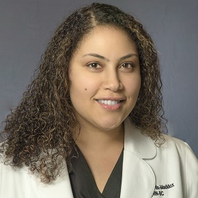Portrait of woman with long brown curly hair wearing a white lab coat